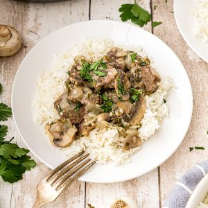 Steak tips with Creamy Mushroom Sauce over rice on a serving plate.