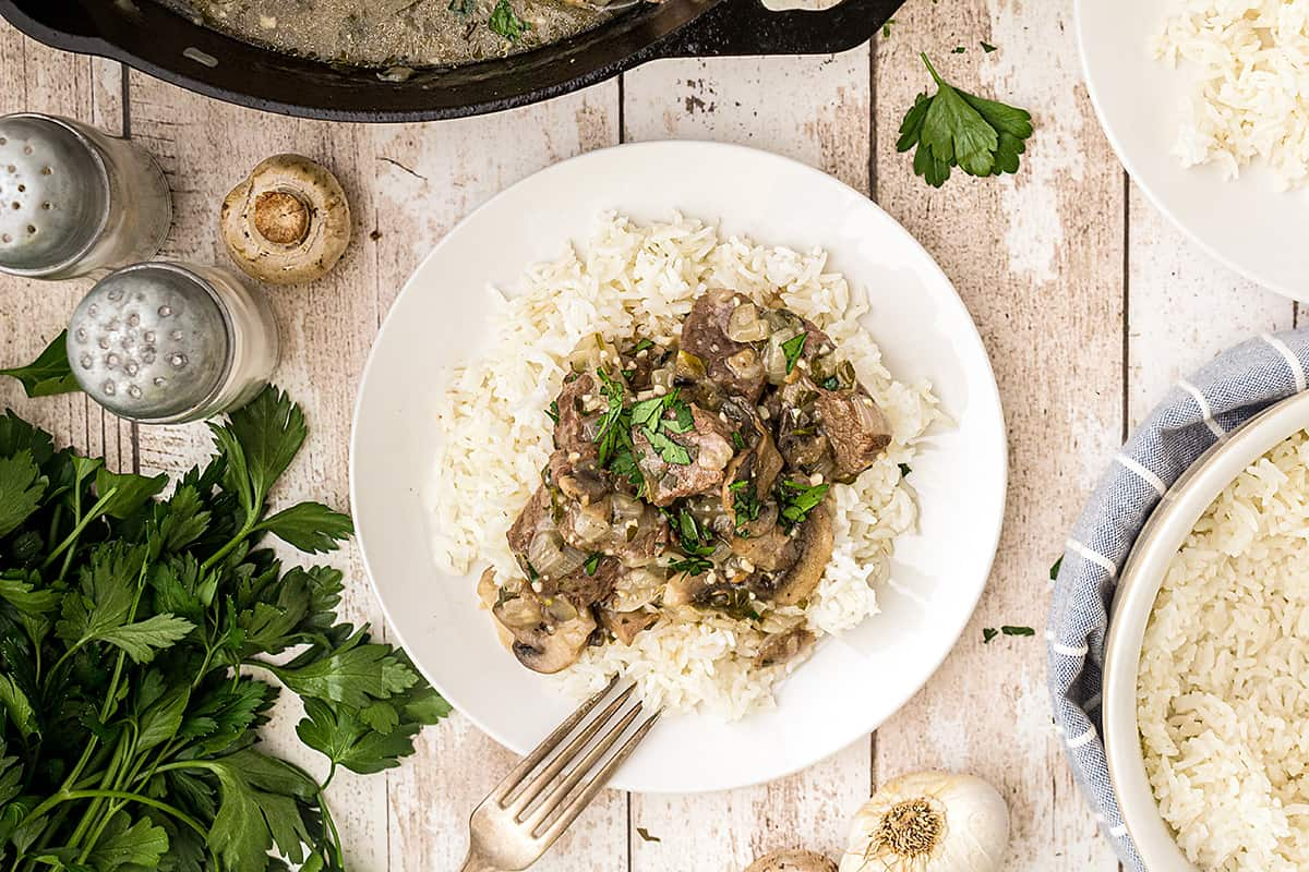 A serving of Steak Tips with Creamy Mushroom Sauce over rice on a white plate.