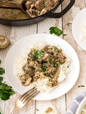 Steak Tips with Creamy Mushroom Sauce over rice on a white dinner plate.