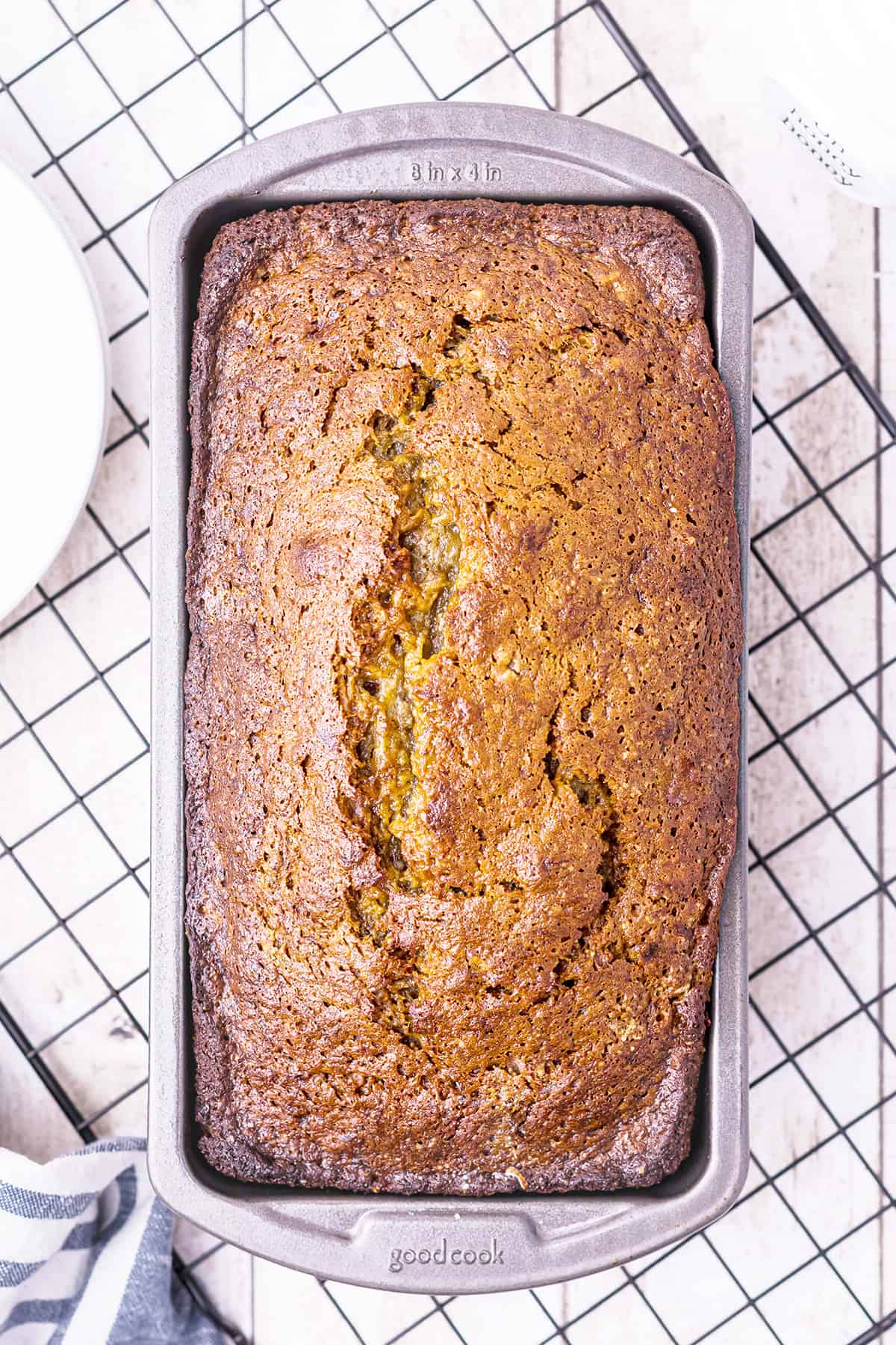 Baked banana nut bread in loaf pan on a cooling rack.