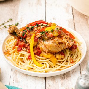 Dutch Oven Chicken Cacciatore over pasta in a white serving bowl on a rustic wooden background.