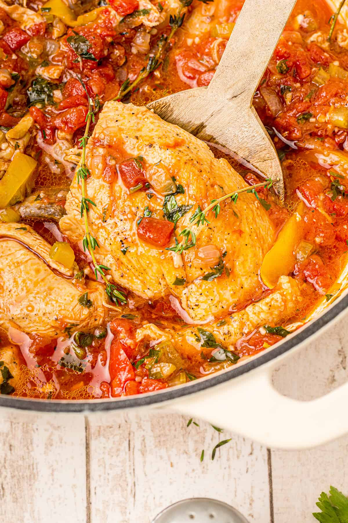 Dutch oven chicken cacciatore in a cooking pot along with a wooden spoon.
