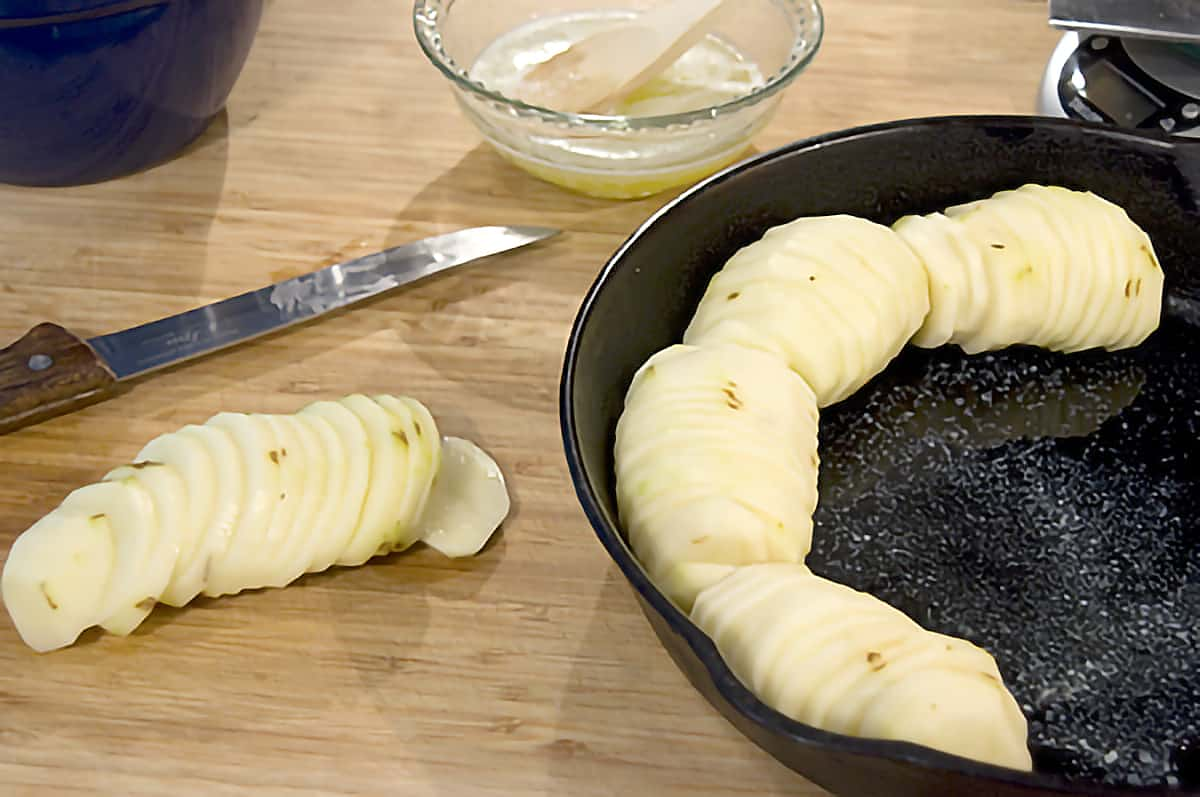 Potatoes peeled and sliced being fitted into a cast iron skillet.