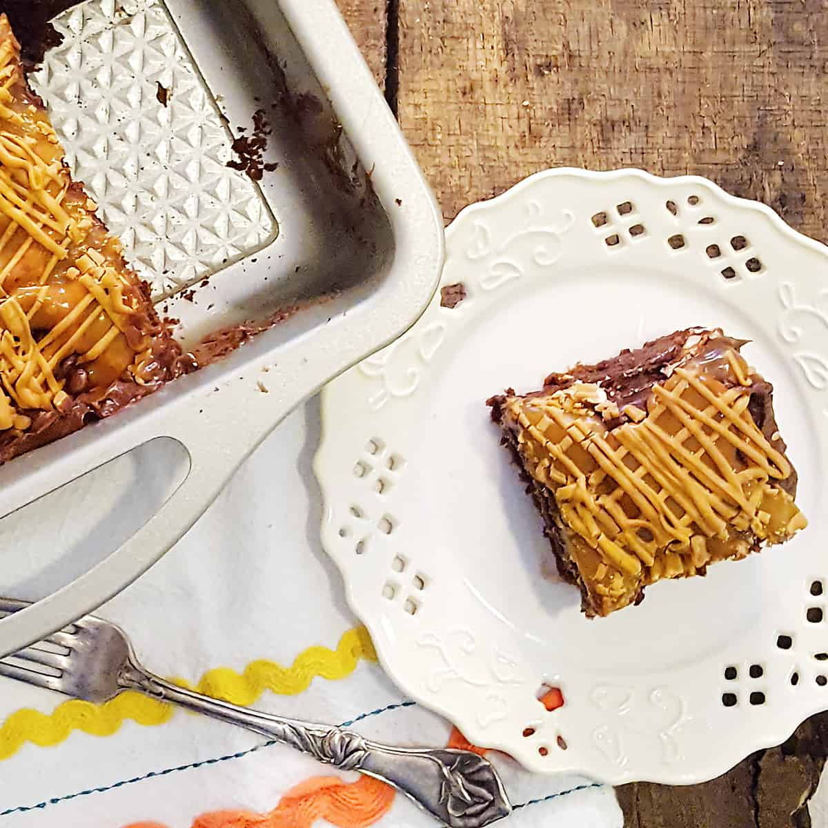 A serving of Easy Caramel Pretzel Brownies on a white serving plate with the full pan of brownies in the background.