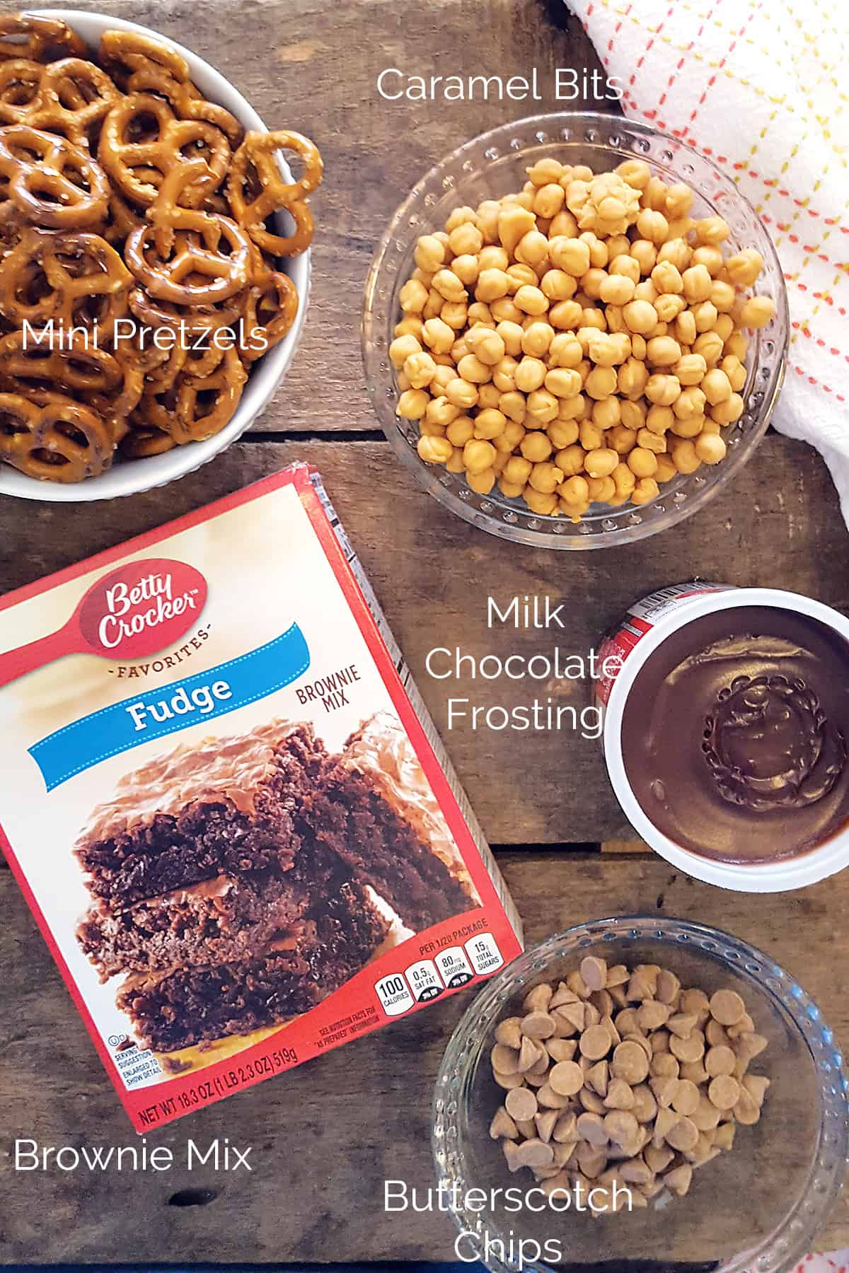 Ingredients needed for Easy Caramel Pretzel Brownies -- mini pretzels, caramel bits, milk chocolate frosting, brownie mix, butterscotch chips.