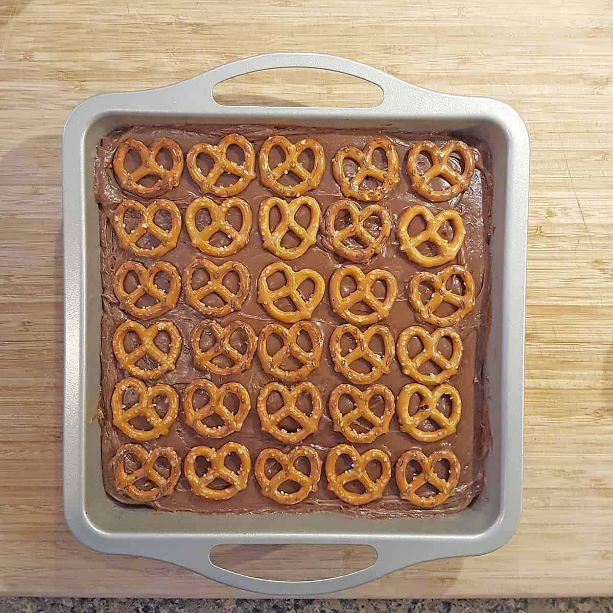 Brownies topped with a layer of milk chocolate frosting and mini pretzels.