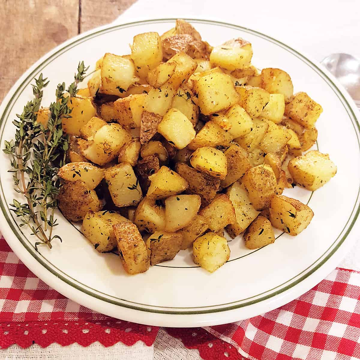 Home Fries on a serving plate with a kitchen towel in the background.
