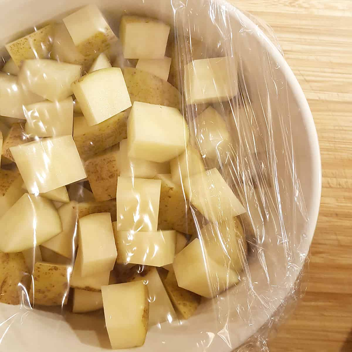 Cubed potatoes in a bowl covered with plastic wrap.