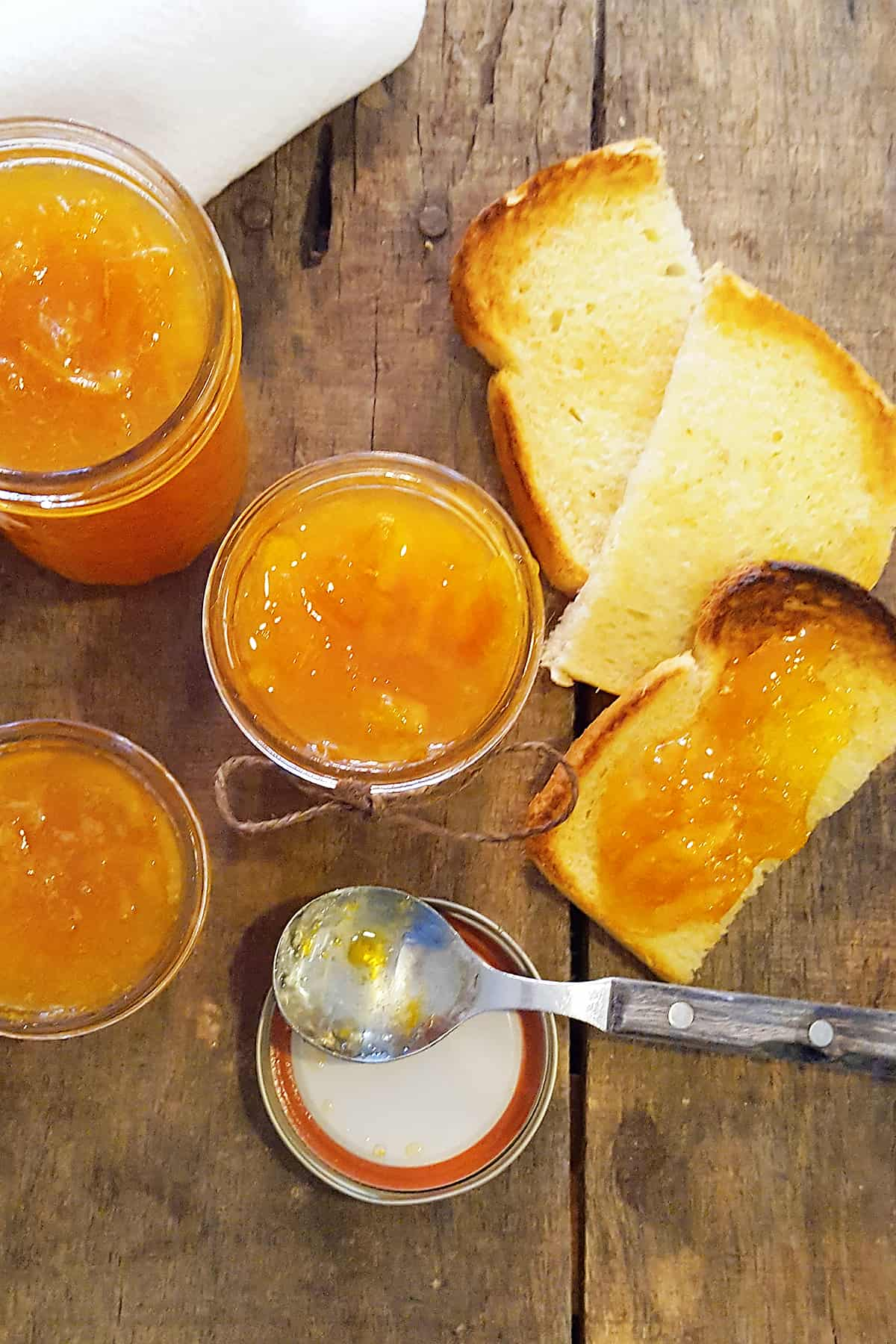 Three jars of orange marmalade with a spoon and toasted bread on a serving board.