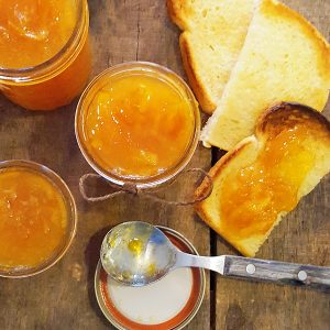 Jars of spiced orange marmalade with a spoon and toasted bread.