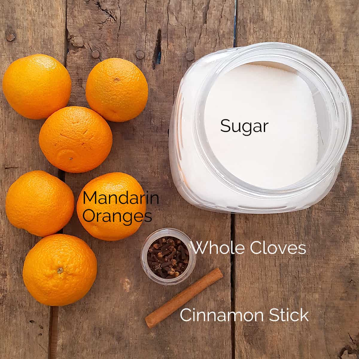 Ingredients needed for the recipe: mandarin oranges, sugar, whole cloves, and cinnamon stick (water not pictured)