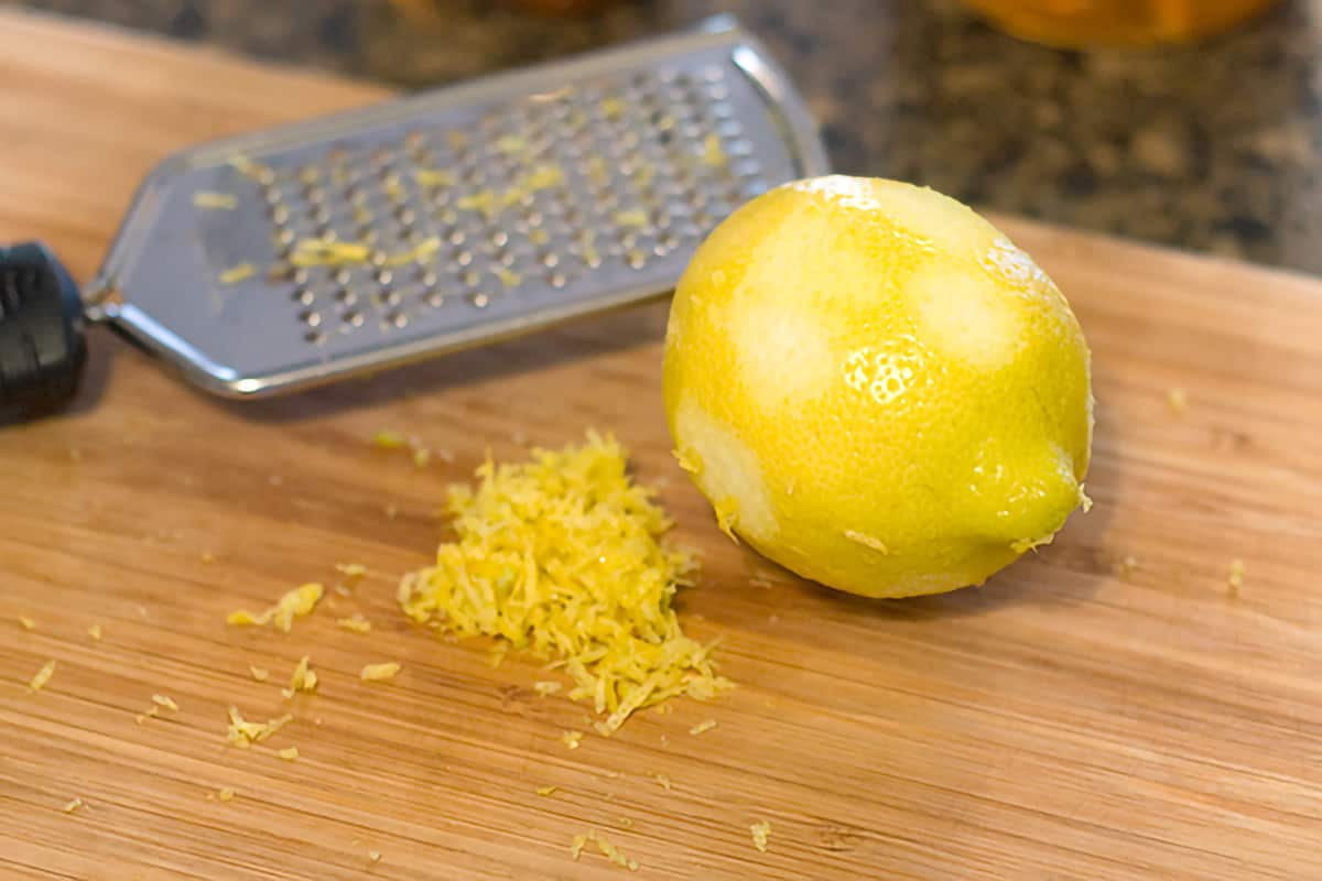 A lemon partly zested with a grated on a cutting board.