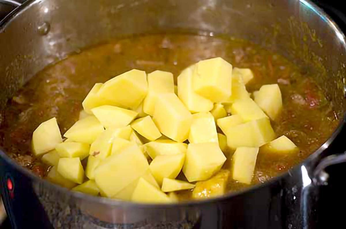 Cooked stew with potatoes added to the pot.