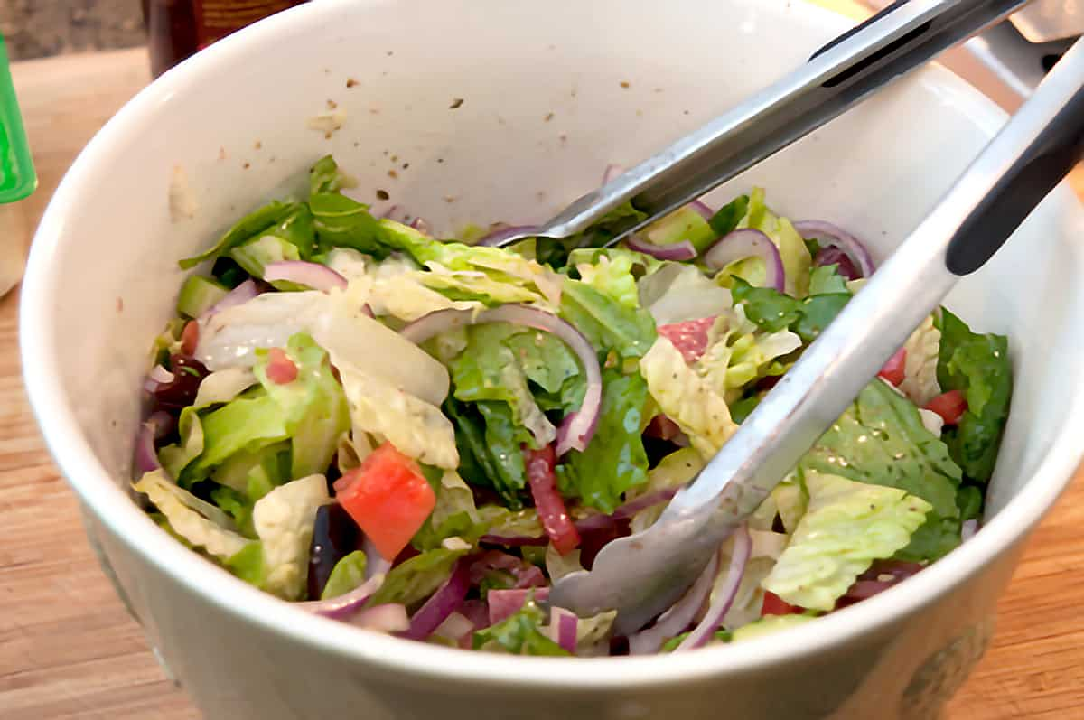 Large salad bowl containing all ingredients for the salad and a pair of cooking tongs.
