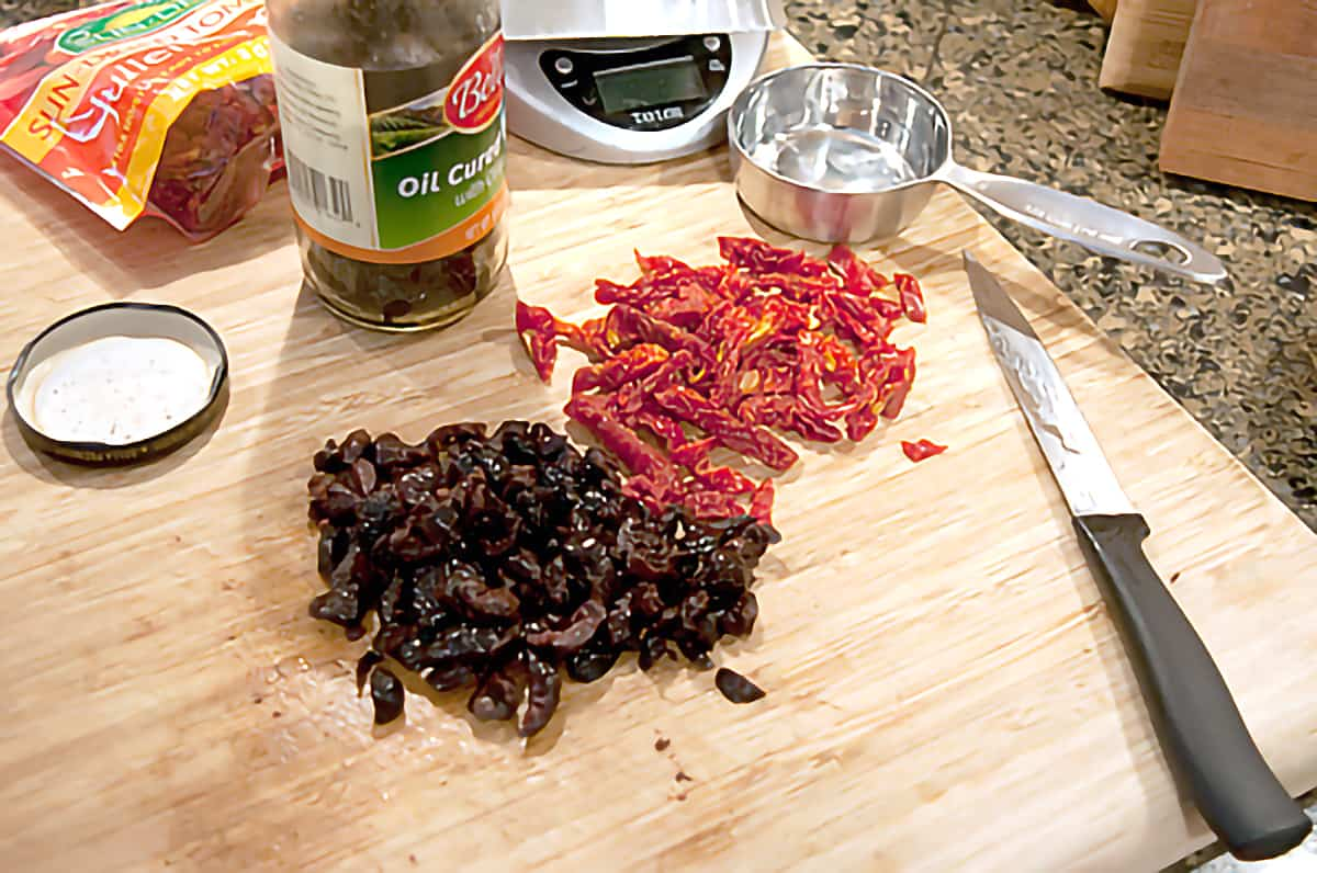 Chopped sun-dried tomatoes and chopped olives on a cutting board.