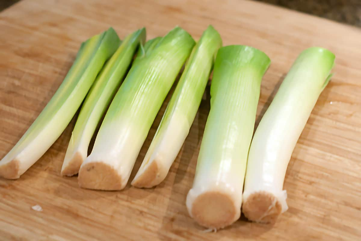 Cleaned and trimmed leeks on a cutting board.