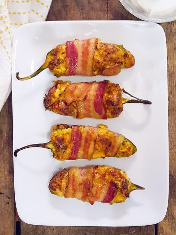 Sausage stuffed bacon wrapped jalapenos on a white serving plate with a kitchen towel and small bowl of sour cream.