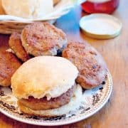 Spicy breakfast sausage patties and biscuits on a serving plate with a jar of jelly in the background.