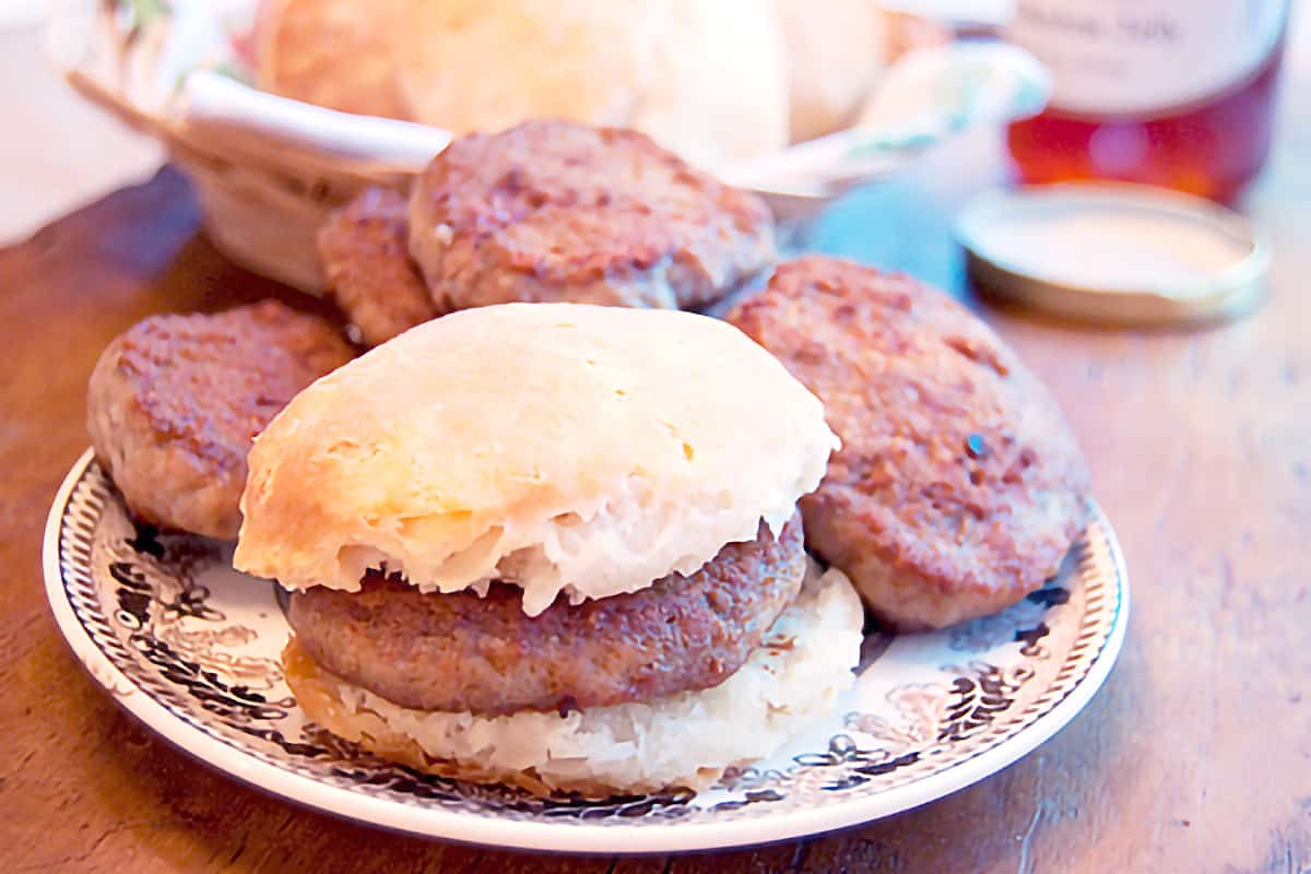 Cooked sausage patties and biscuits on a serving plate.