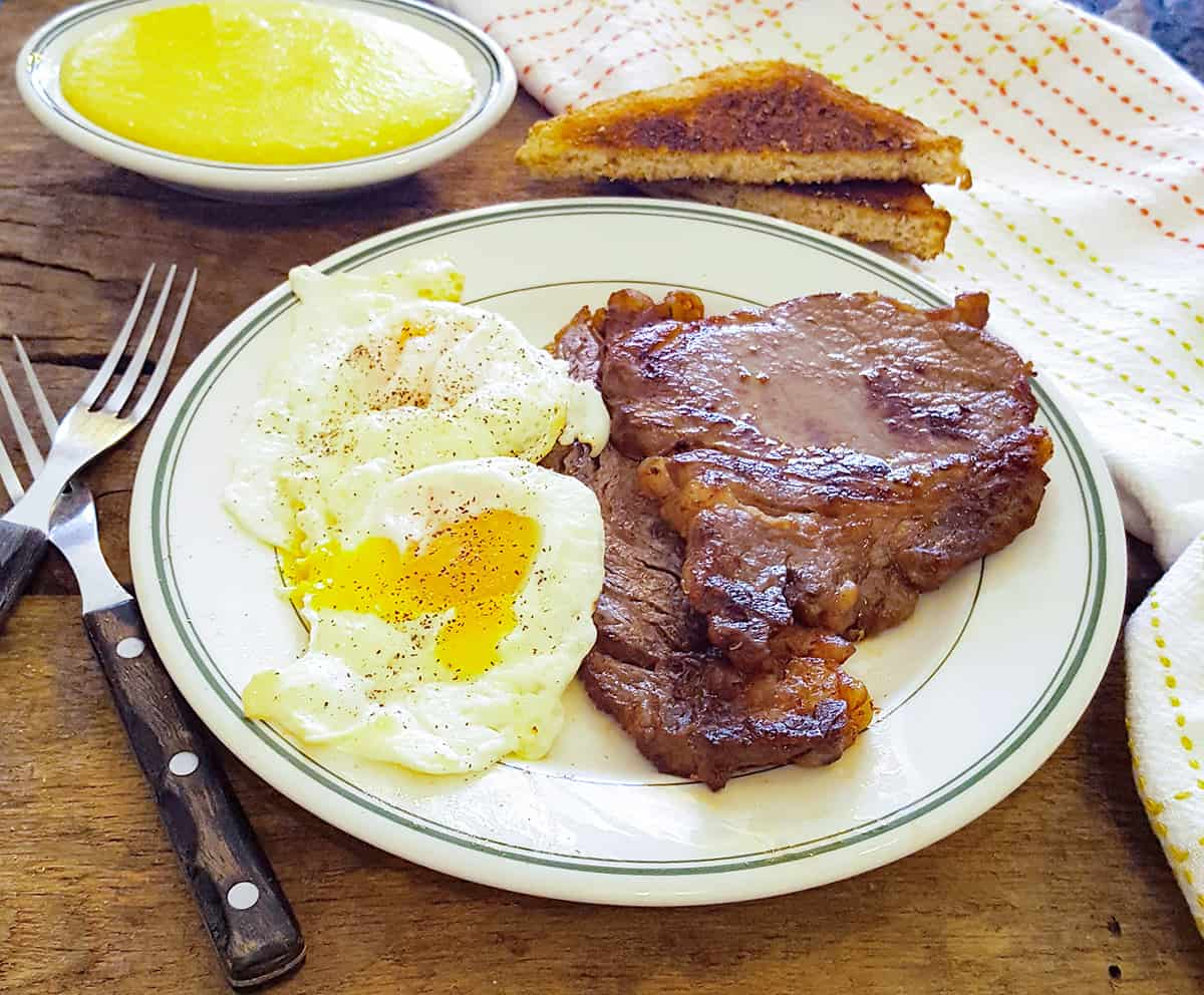 Steak and eggs on a serving plate with toast and grits alongside.