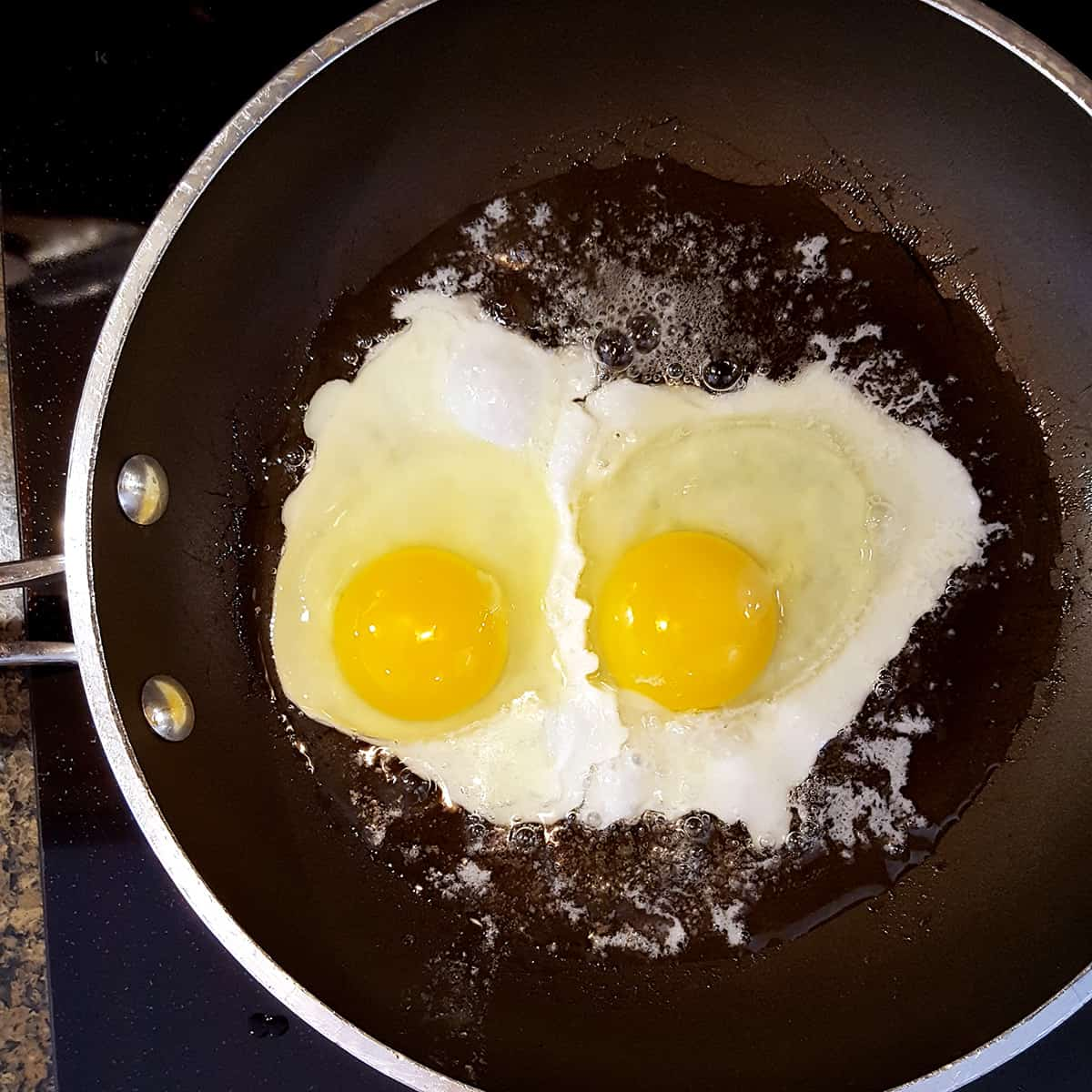 Two eggs cooking in a skillet with butter and oil.