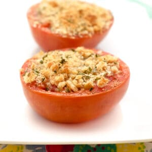 Tomatoes topped with breadcrumbs and herbs on a serving plate.