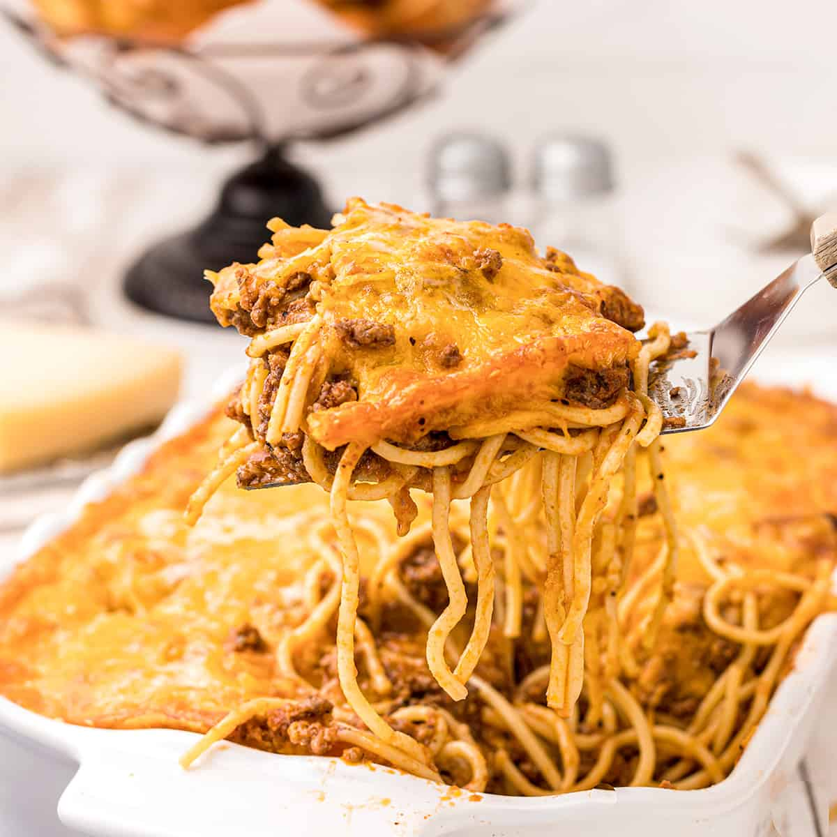 A forkful of baked spaghetti dripping with cheesy topping and meat sauce.