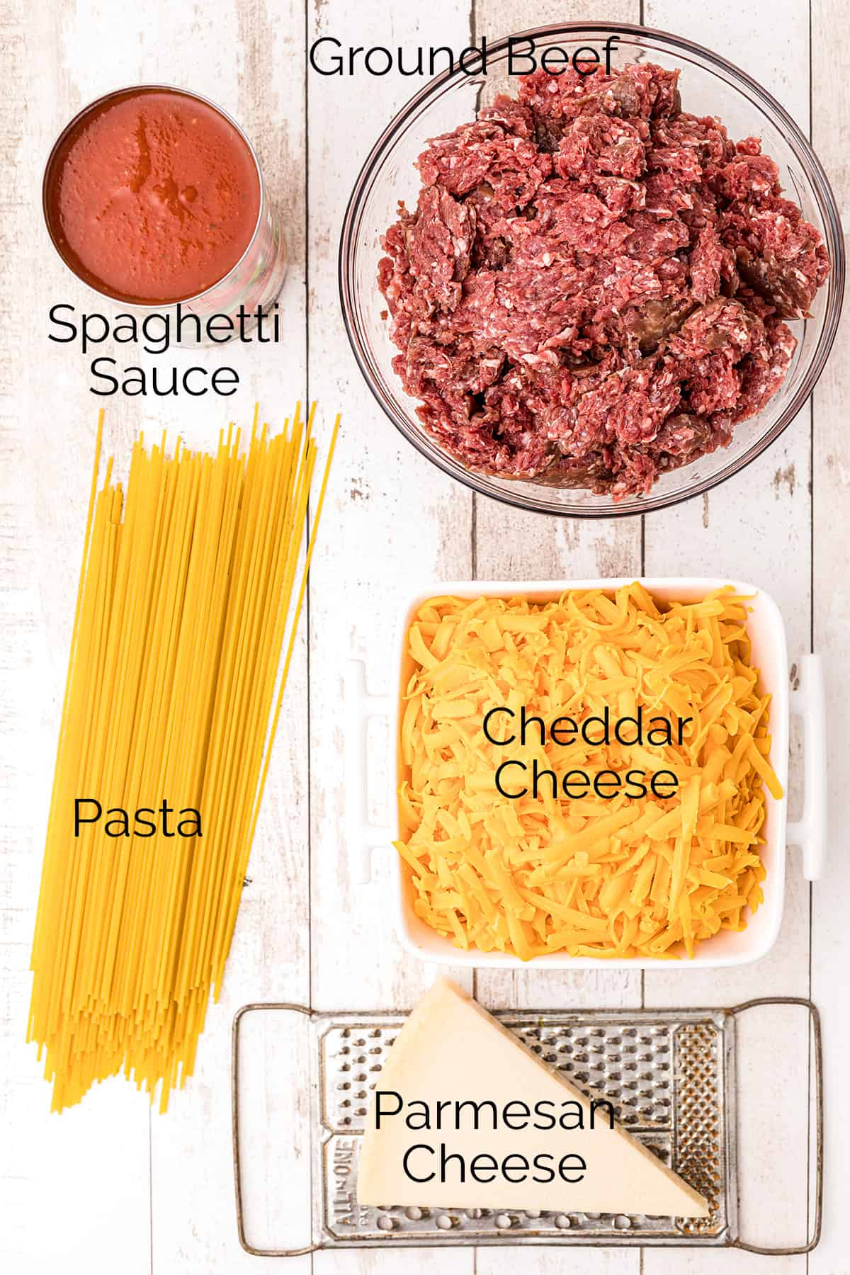 The five ingredients needed for the recipe - spaghetti sauce, ground beef, pasta, cheddar cheese, parmesan cheese.