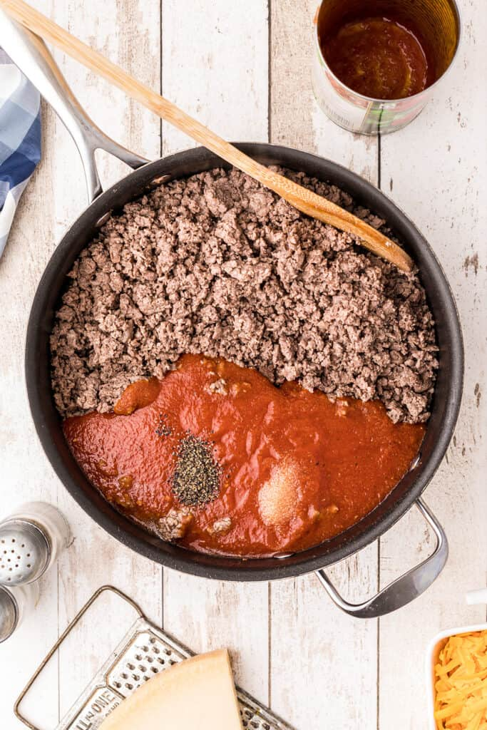 Spaghetti sauce, salt and pepper added to ground beef in skillet.