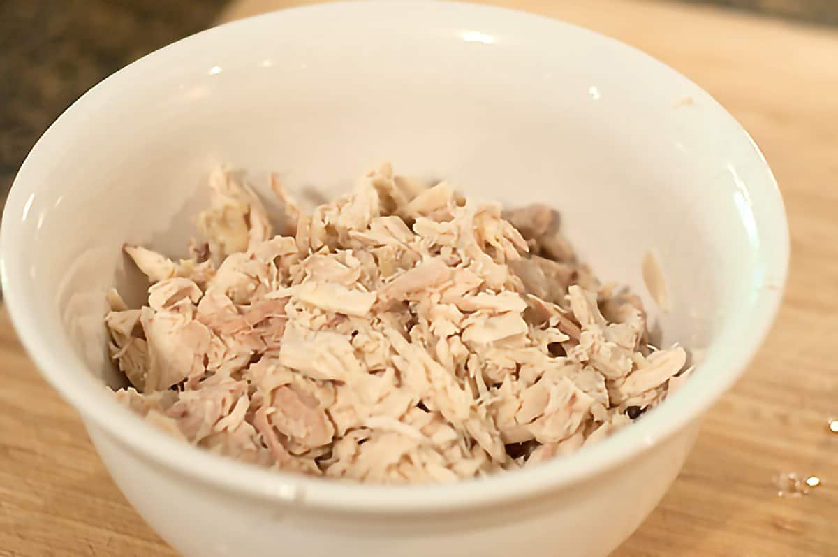 Shredded, deboned chicken in a white bowl.