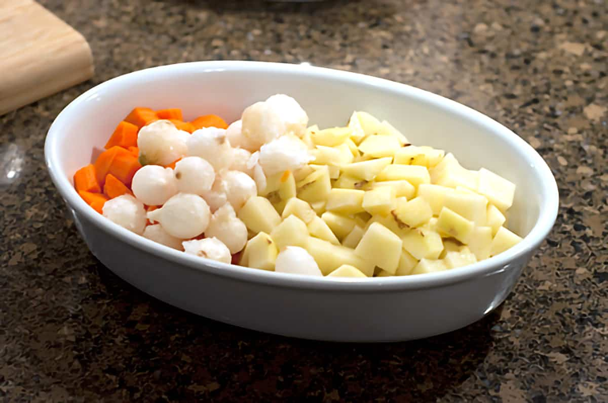 Carrots, potatoes, and pearl onions in a ceramic baking dish.