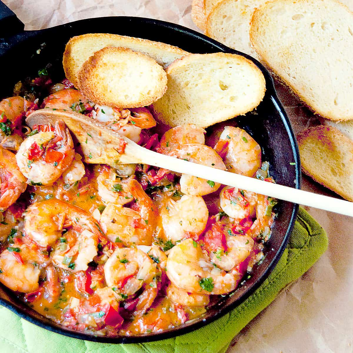 Cilantro Lime Shrimp in a cast iron skillet with garlic bread on the side.