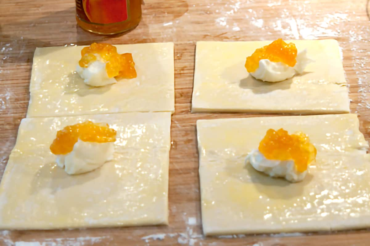 Four puff pastry squares each topped with cream cheese mixture and peach preserves.