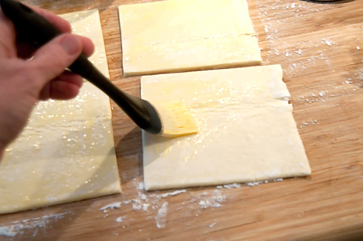 Pastry squares being brushed with egg wash.