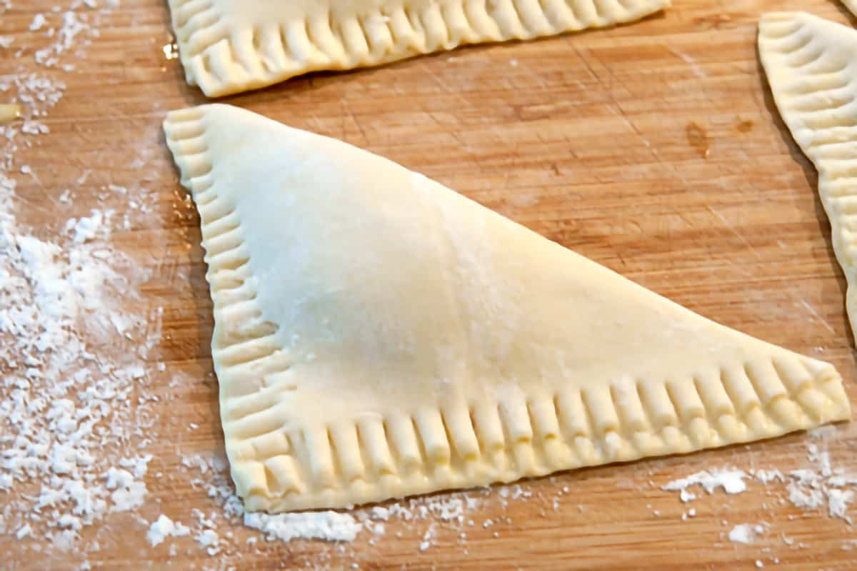 A closeup view of pastry triangles with crimped edges.