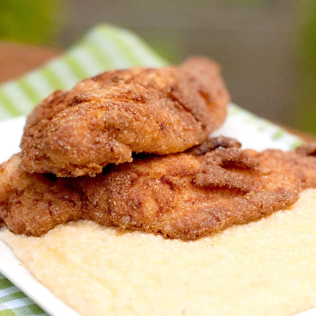 Fried catfish on a platter of cheese grits.