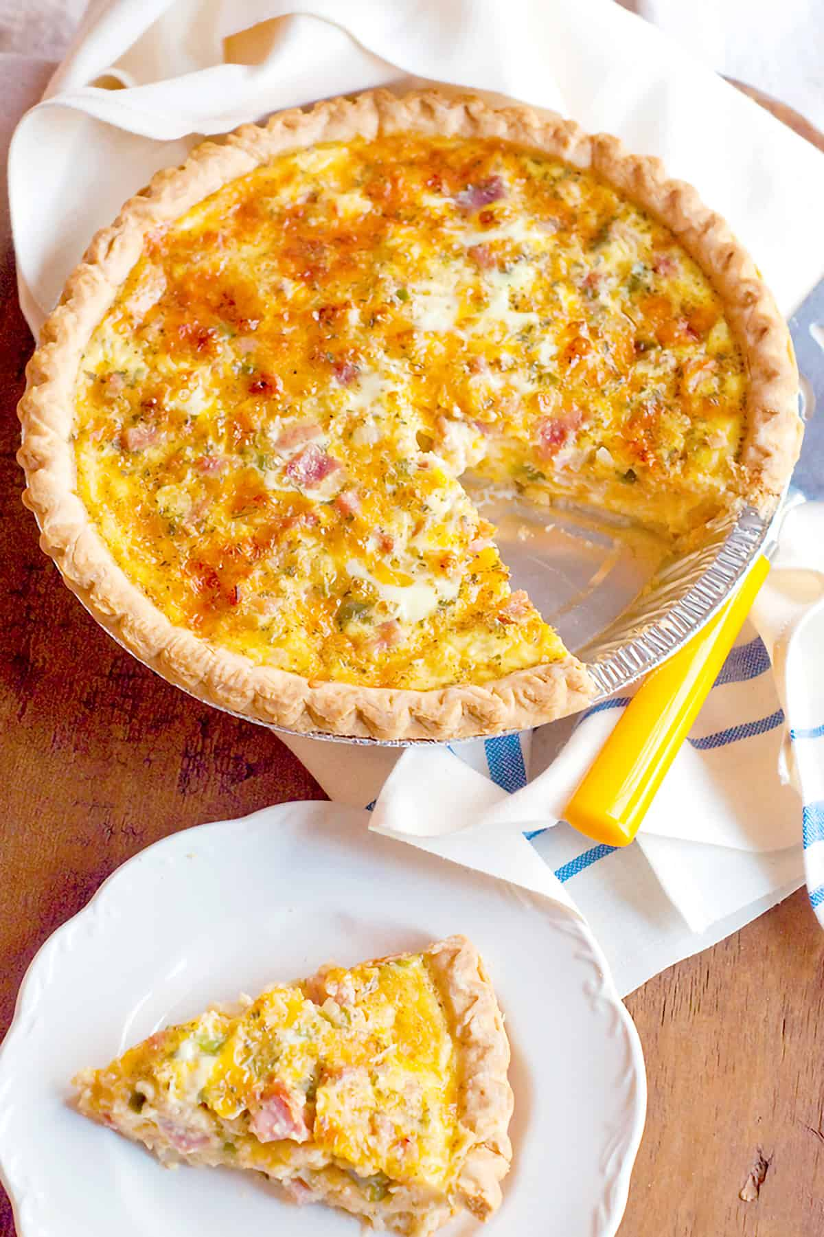 Ham and cheese quiche on a kitchen towel.