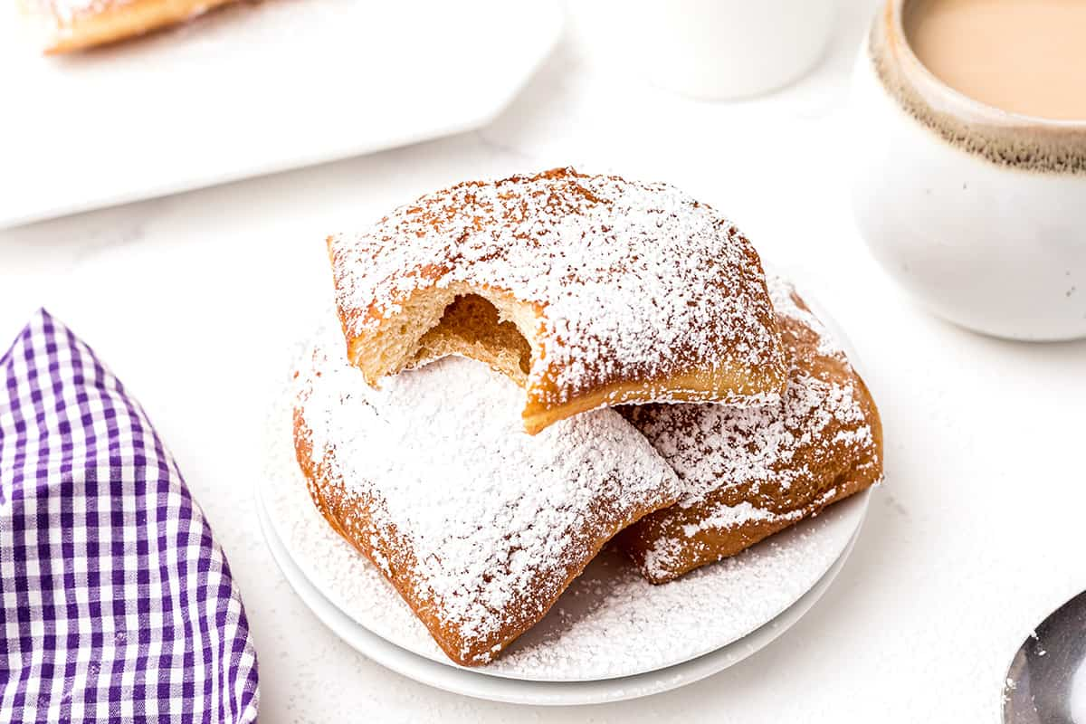 A serving of beignets topped with powdered sugar with cafe au lait to the side.