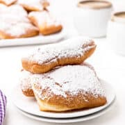 A serving of beignets topped with powdered sugar with a cafe au lait in the background.
