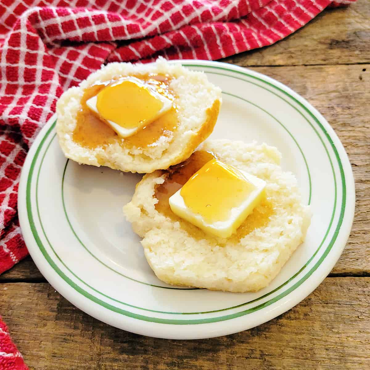 A split biscuit filled with butter and drizzled with honey.