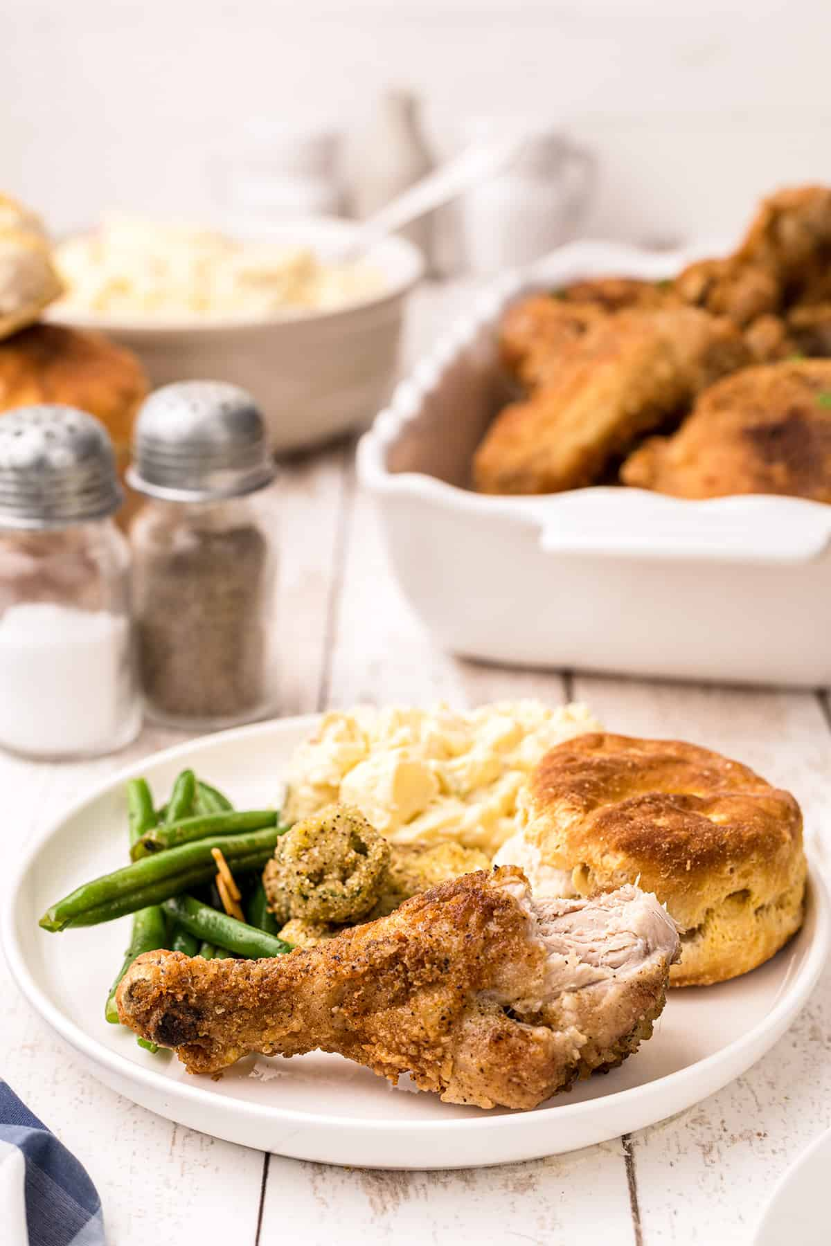 Fried chicken leg on a white dinner plate with green beans, okra, potatoes, and biscuits.