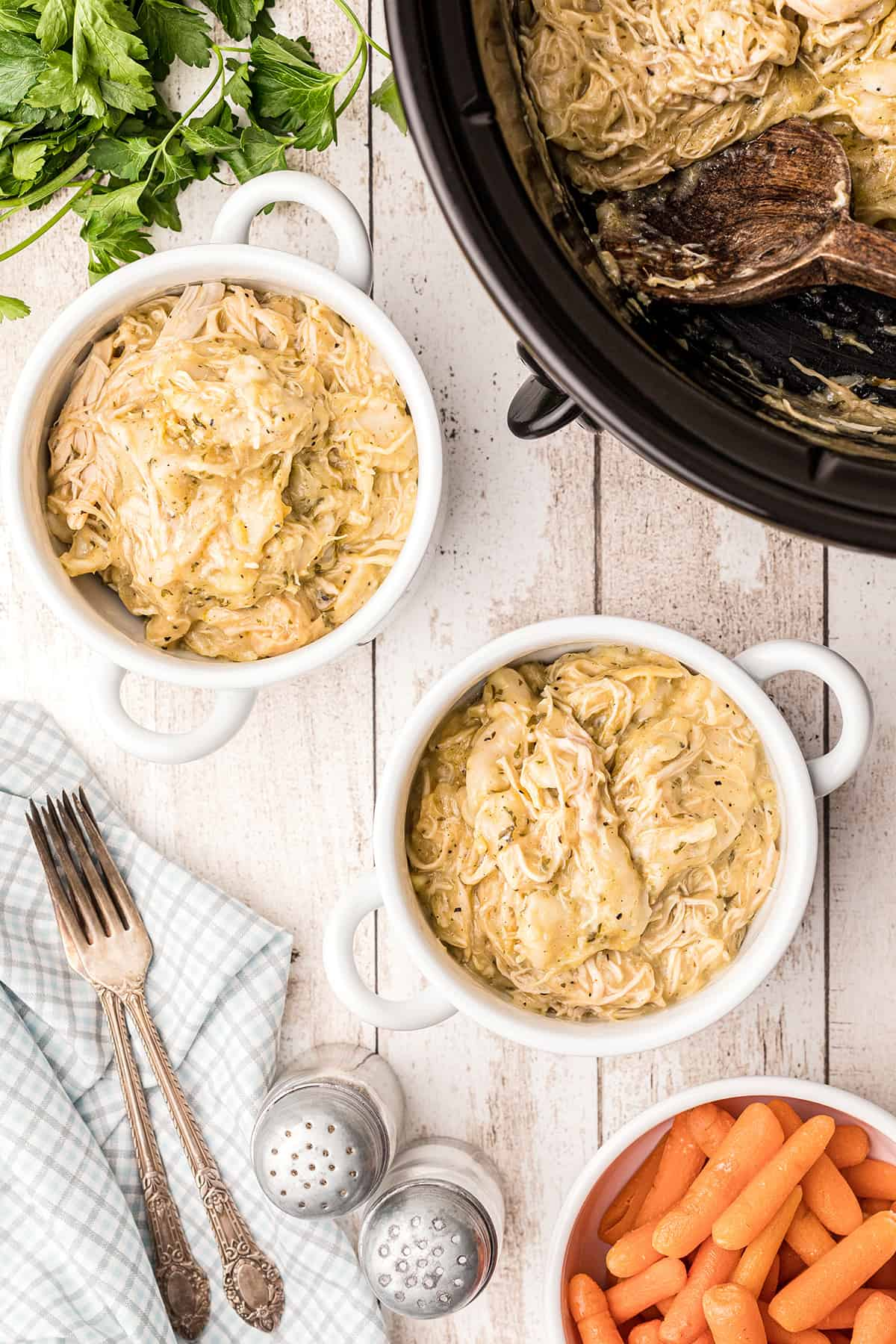 Two servings of chicken and dumplings in white bowls with a slow cooker in the background.