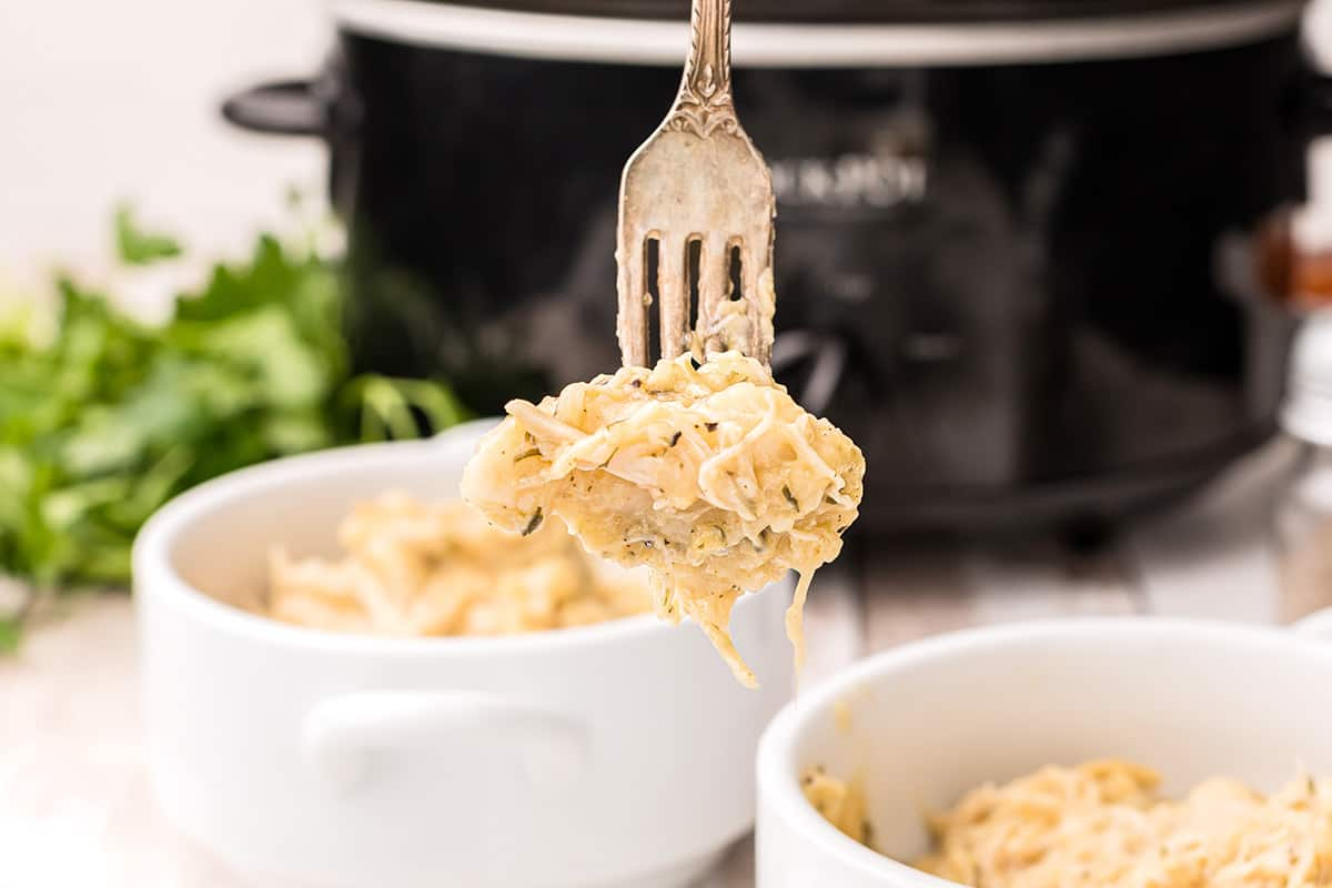 A forkful of slow cooker chicken and dumplings with a slow cooker in the background.