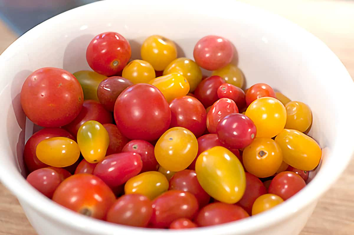 Yellow and red cherry tomatoes in a white mixing bowl.