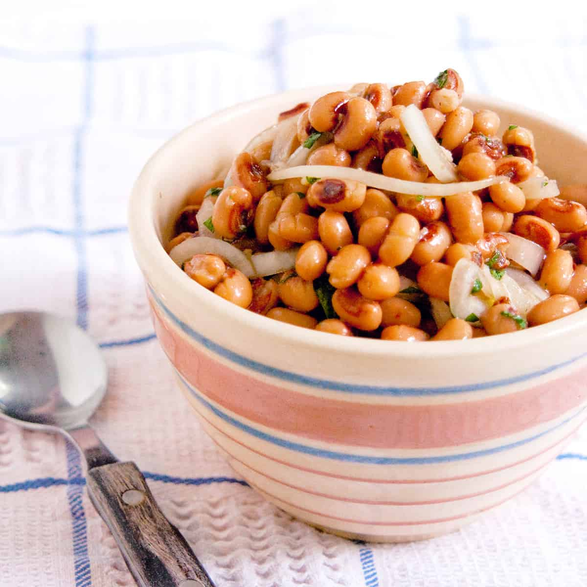 Black Eyed Pea Salad in a vintage serving bowl set on a kitchen towel.