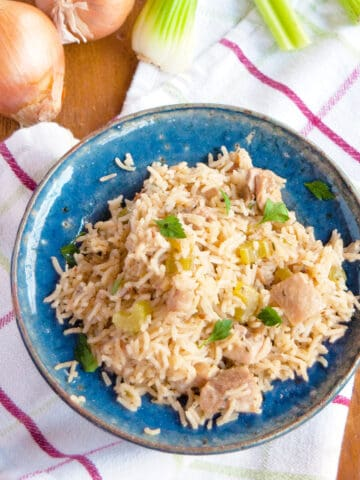 Chicken and rice in a blue bowl on a wooden board.