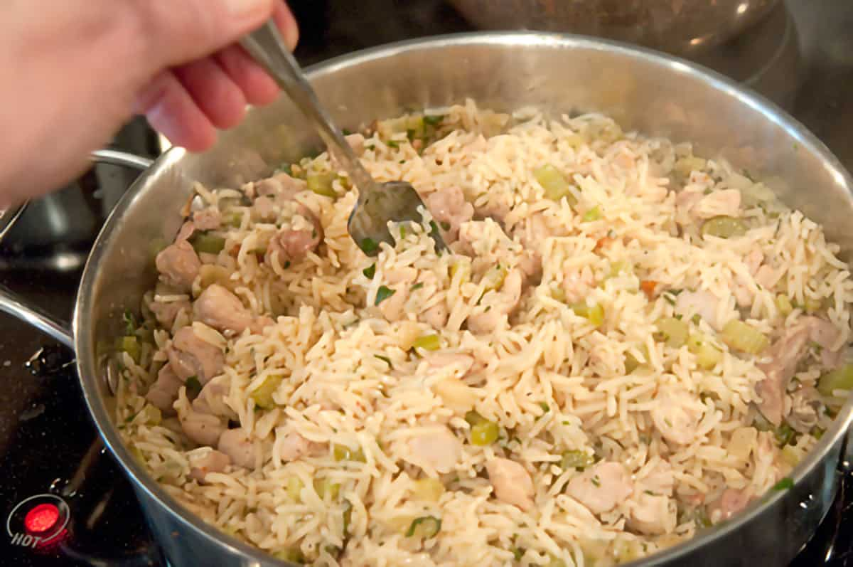 Finished chicken and rice in a skillet being fluffed with a fork.