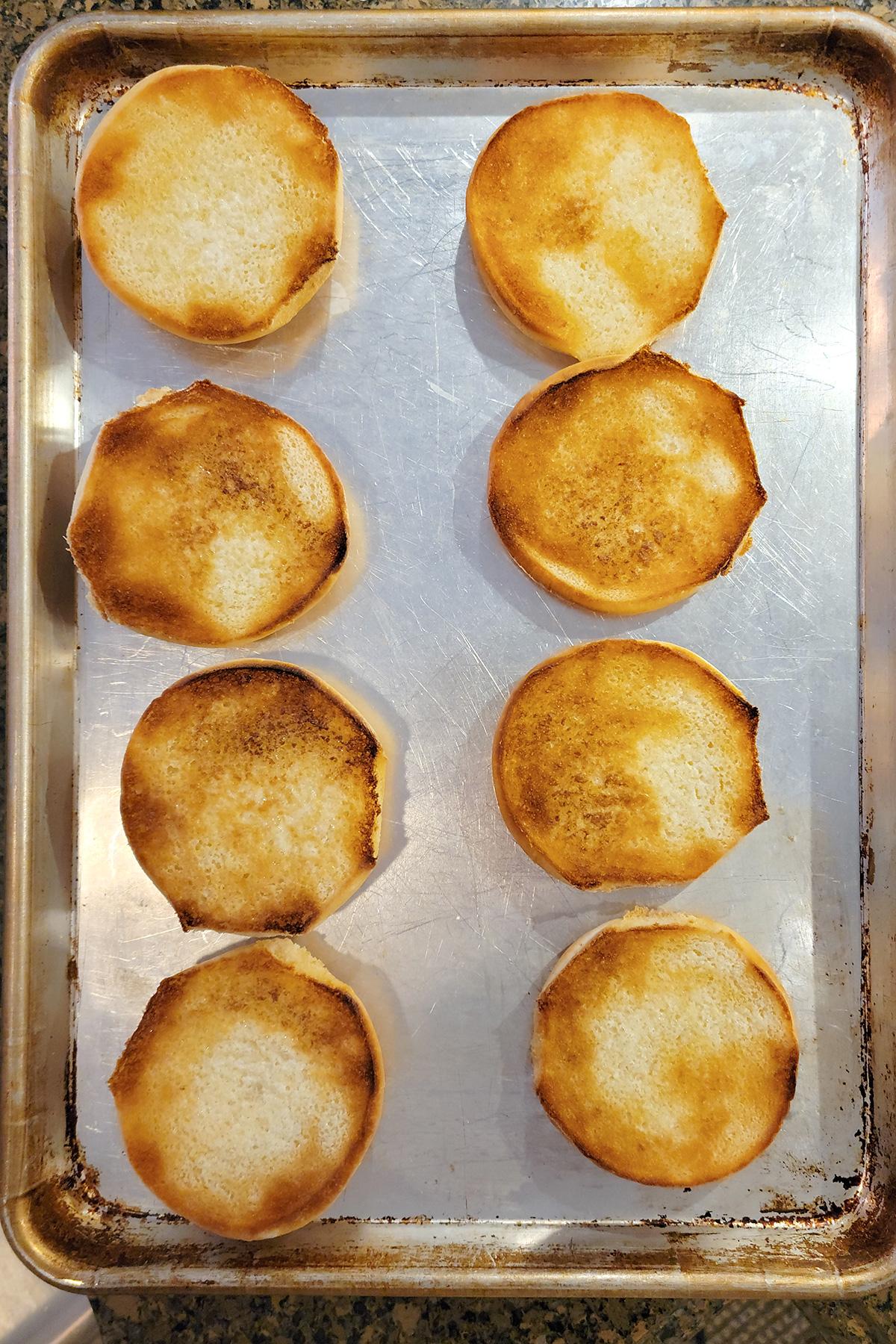 Hamburger buns on a baking sheet after toasting.