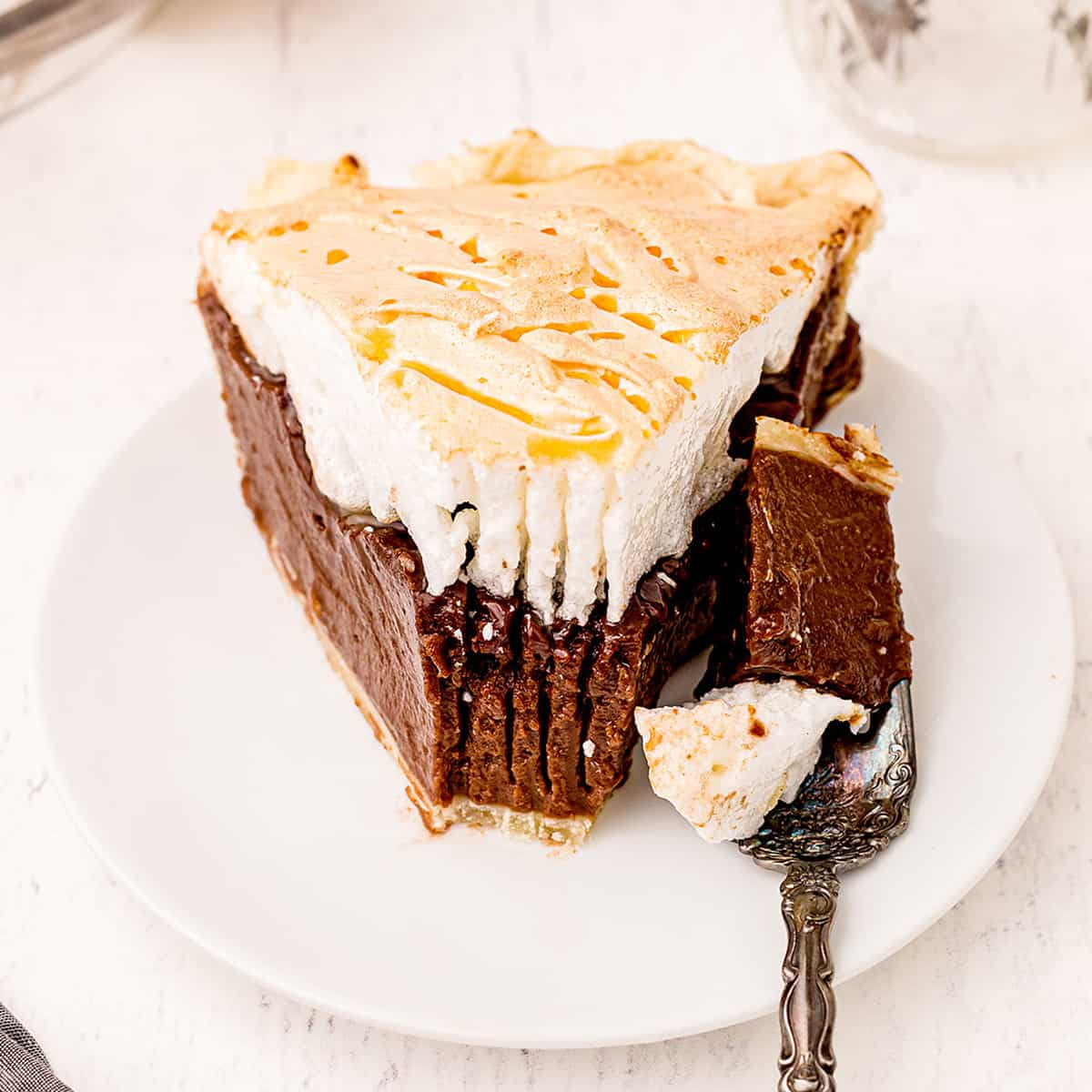 A slice of old fashioned chocolate meringue pie on a white serving plate.