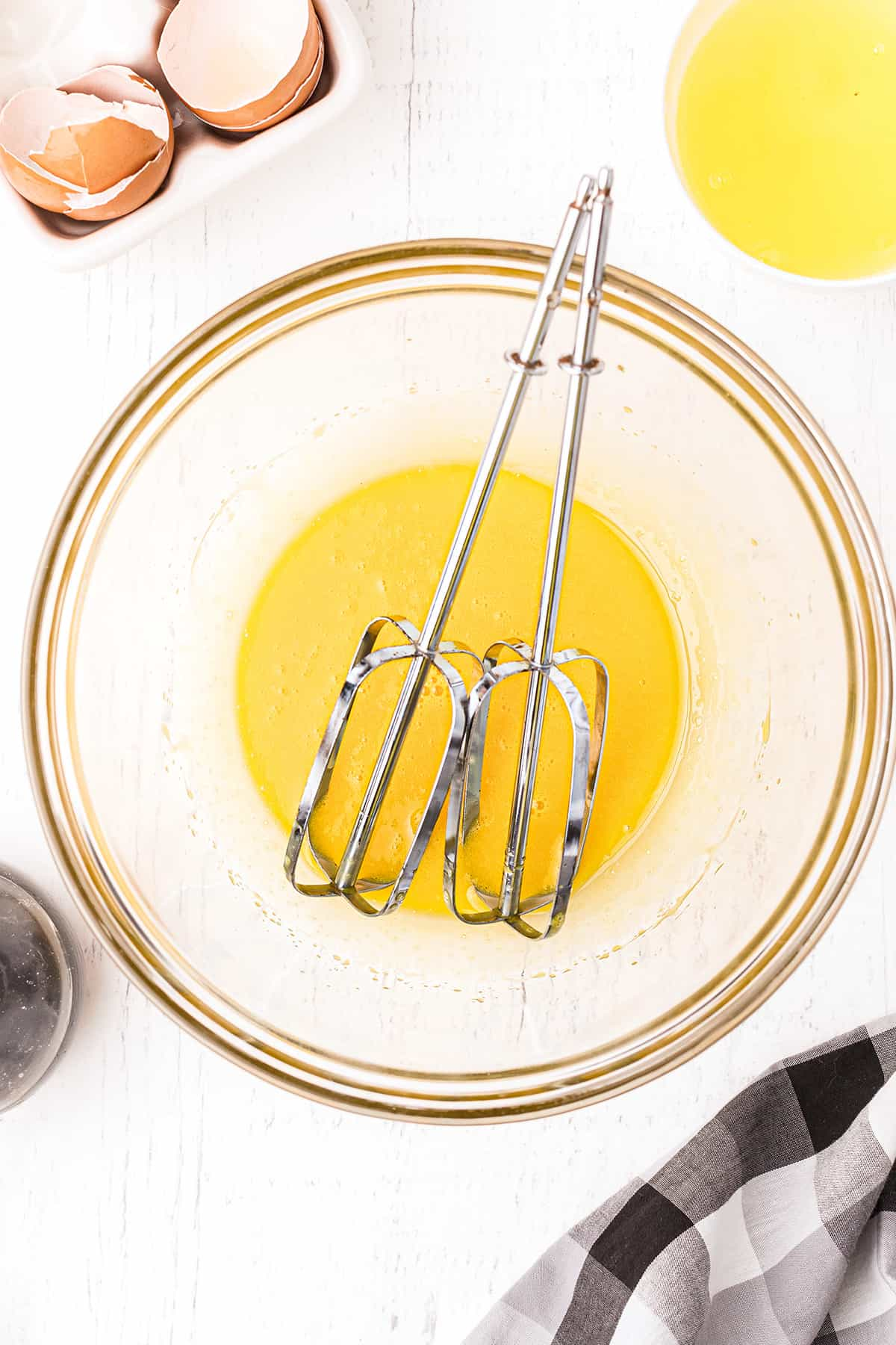A mixing bowl holding egg yolks and mixer beaters.
